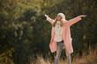 Happy and cheerful woman enjoying autumn, she raise hands