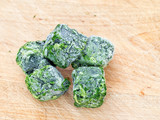 Frozen spinach on wooden cutting board. - 175473029