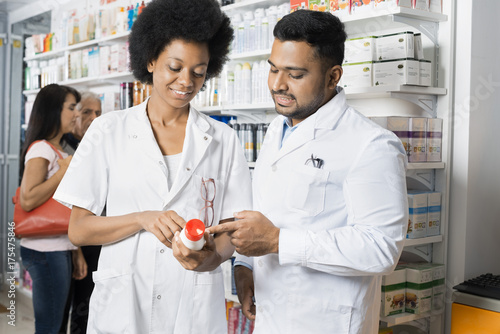 Chemists Discussing About Product While Customers Shopping