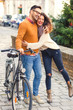 Happy young couple with a bicycle on sunny autumn day in the city. - 175477848