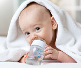 Happy baby drinks water from bottle wrapped towel after bath