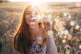 Young woman in summer dress blowing soap bubbles on sunset - 175482663
