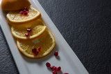 Slice of orange with pomegranate seeds in tray - 175482833