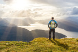 Fototapety Man reaching summit enjoying freedom. Stunning view to coastal mountains and fjords. Hellandsnuten, Sandsfjord, Norway.