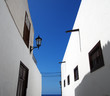 street of traditional white houses in perspective view looking upwards with bright blue summer sky leading to the sea