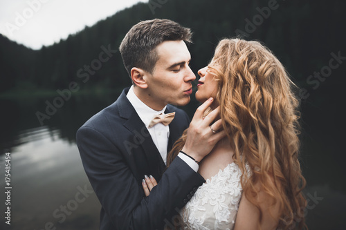 Fotobehang Grijze traf. Beautifull wedding couple kissing and embracing near mountain with perfect view