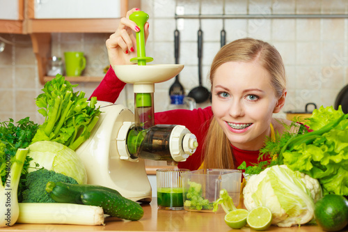 In de dag Sap Woman in kitchen making vegetable smoothie juice