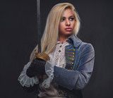 An attractive blonde female holds a silver sword. - 175488609