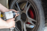 Mechanic unscrews automobile wheel with pneumatic tool - 175493252