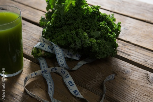 Staande foto Sap Mustard greens, measuring tape and juice on wooden table