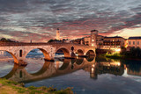 Roman empire ancient bridge Ponte Pietra over the river Adige in Verona, Italy during sunset with illuminated old town - 175495477