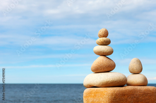 Staande foto Zen Stones balance on a background of blue sky and sea