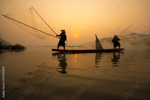 Two fishermen are fishing on the boat at Mekong river in the morning in Nong Khai, Thailand