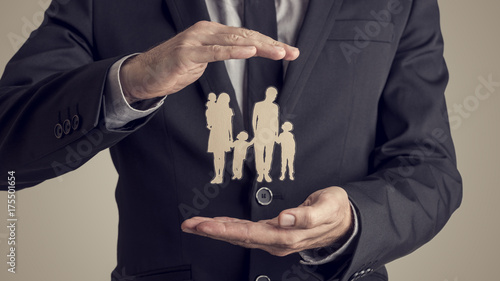 Retro style image of a businessman protecting family silhouette - 175501654