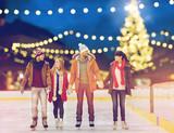 happy friends at christmas skating rink - 175503404