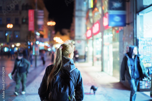 Sticker Back view of girl walking on city street at night, Prague