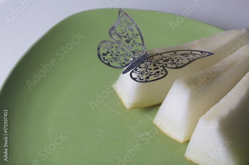Juicy slices of melon lie on a green plate. On them is a decoration, a butterfly cut from a foil. - 175507453