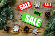 Christmas sale. Sale labels near spruce branch and xmas decor on wooden background top view