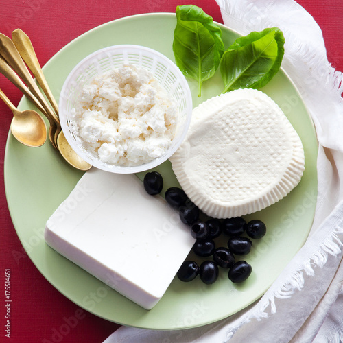 group of white cheeses: ricotta, Sicilian primosale and sheep cheese on the plate. appetizers with olives
