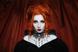 A woman is a vampire with pale skin and red hair in a black dress and a necklace on her neck. Girl witch with vampire claws and red lips. Gothic look. Outfit for halloween. - 175515689