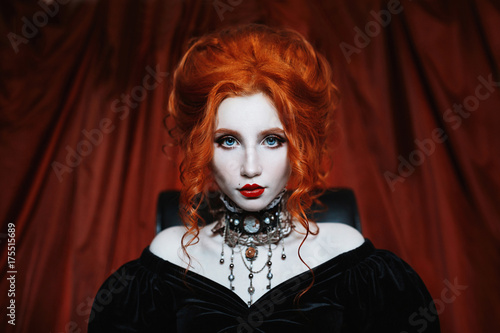 Poster A woman is a vampire with pale skin and red hair in a black dress and a necklace on her neck