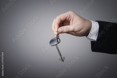 Businessman's hand holding a key Poster