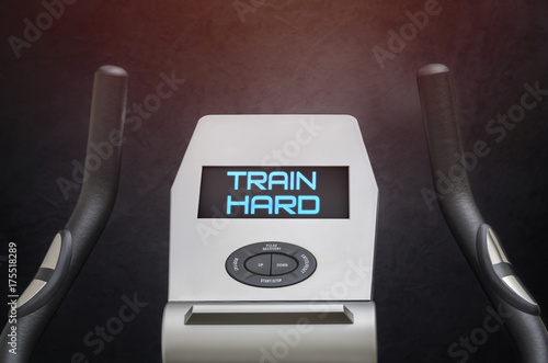 Train hard text on exercise bike lcd screen. Poster