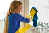 Girl cleaning window at home using detergent rag - 175522459