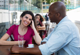 Caucasian woman flirting with african american man at restaurant - 175528429