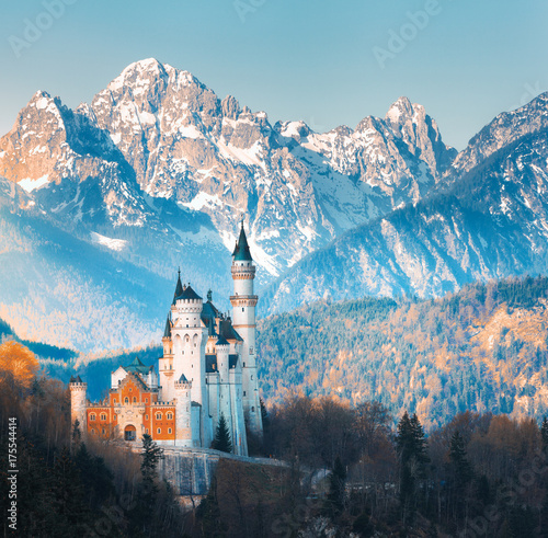 The famous Neuschwanstein Castle in the background of snowy mountains at sunset in Germany. Beautiful autumn landscape with castle, mountain peaks and trees. Landmarks in Europe. Travel. Vintage style