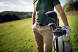 Quadro Golf player walking and carrying bag on course during summer game golfing