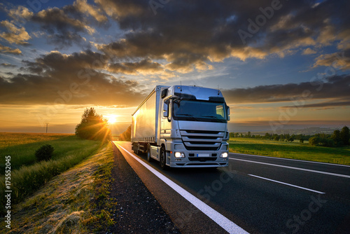 Fototapeta Truck driving on the asphalt road in rural landscape at sunset with dark clouds