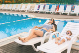Endless summer. Cute baby and mother relaxing at sunbed - 175559405