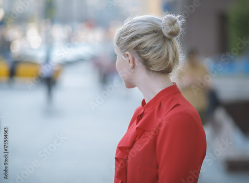 Poster Outdoors portrait of beautiful young woman in a red blouse. Selective focus.