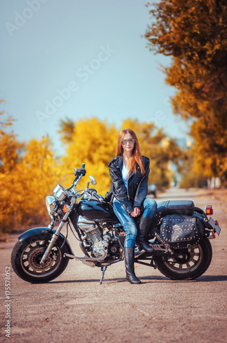 beautiful girl in a leather jacket and blue jeans in a glasses on a motorbike