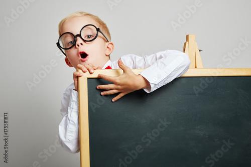 Kind als Schüler hinter einer Tafel