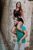 Man carrying his girlfriend on his shoulders. Alternative couple. - 175582026