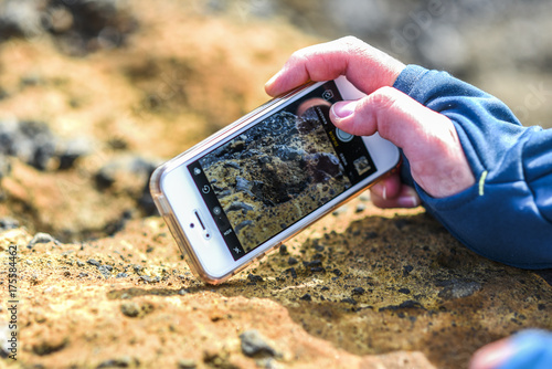 A female hand holding a telephone and photographing a rock.
