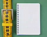 meter belt slimming and notepad on the green background - 175587225