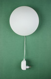 round white lamp with electric plug on a green wall - 175587612