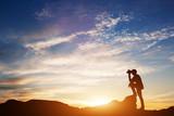 Man looking through binoculars at sunset. - 175593481