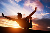 Young man lying on skateboard at sunset. - 175594803