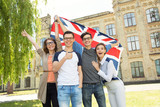 Group of students holding a flag of Great Britain on the university campus background. - 175604209