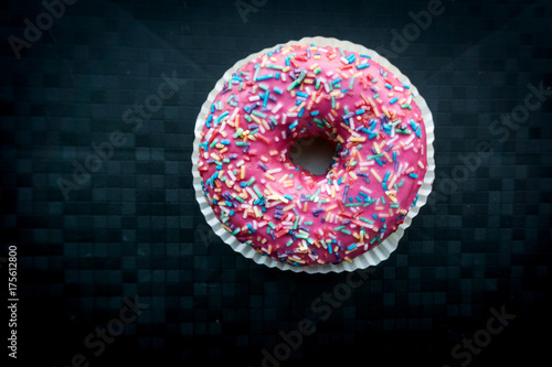 Pink donut with colorful sprinkles isolated on background Poster