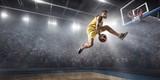 Koszykarz robi slam dunk na dużej profesjonalnej arenie. Gracz leci w powietrzu z piłką. Gracz nosi ubrania niemarkowe.