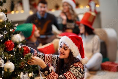 Woman decorates Christmas tree for Christmas eve