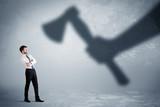 Businessman afraid of a huge shadow hand holding an axe concept - 175641296
