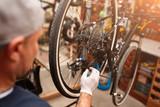 Fototapety Mechanic repairing bicycle in his workshop