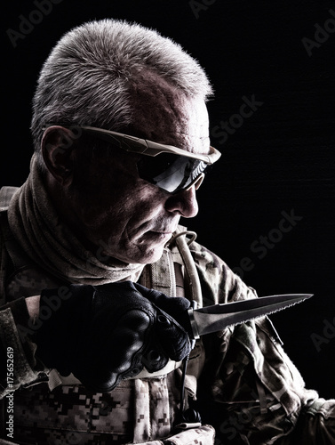 Close up studio shot of special forces white-haired veteran with knife Poster
