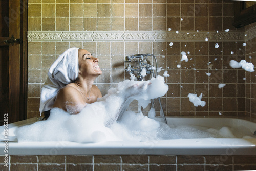 Póster Portrait of happy young woman playing with foam in bathtub